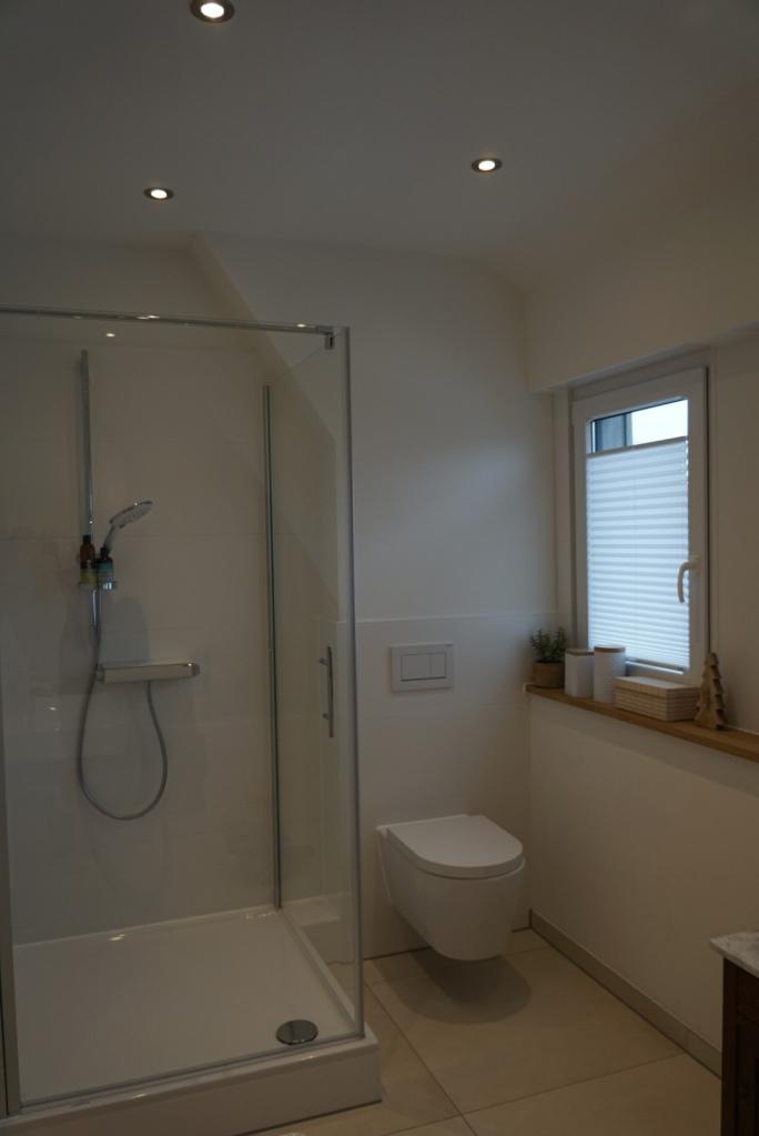 Modernes, helles Bad mit Glastür-Dusche nach der Kernsanierung